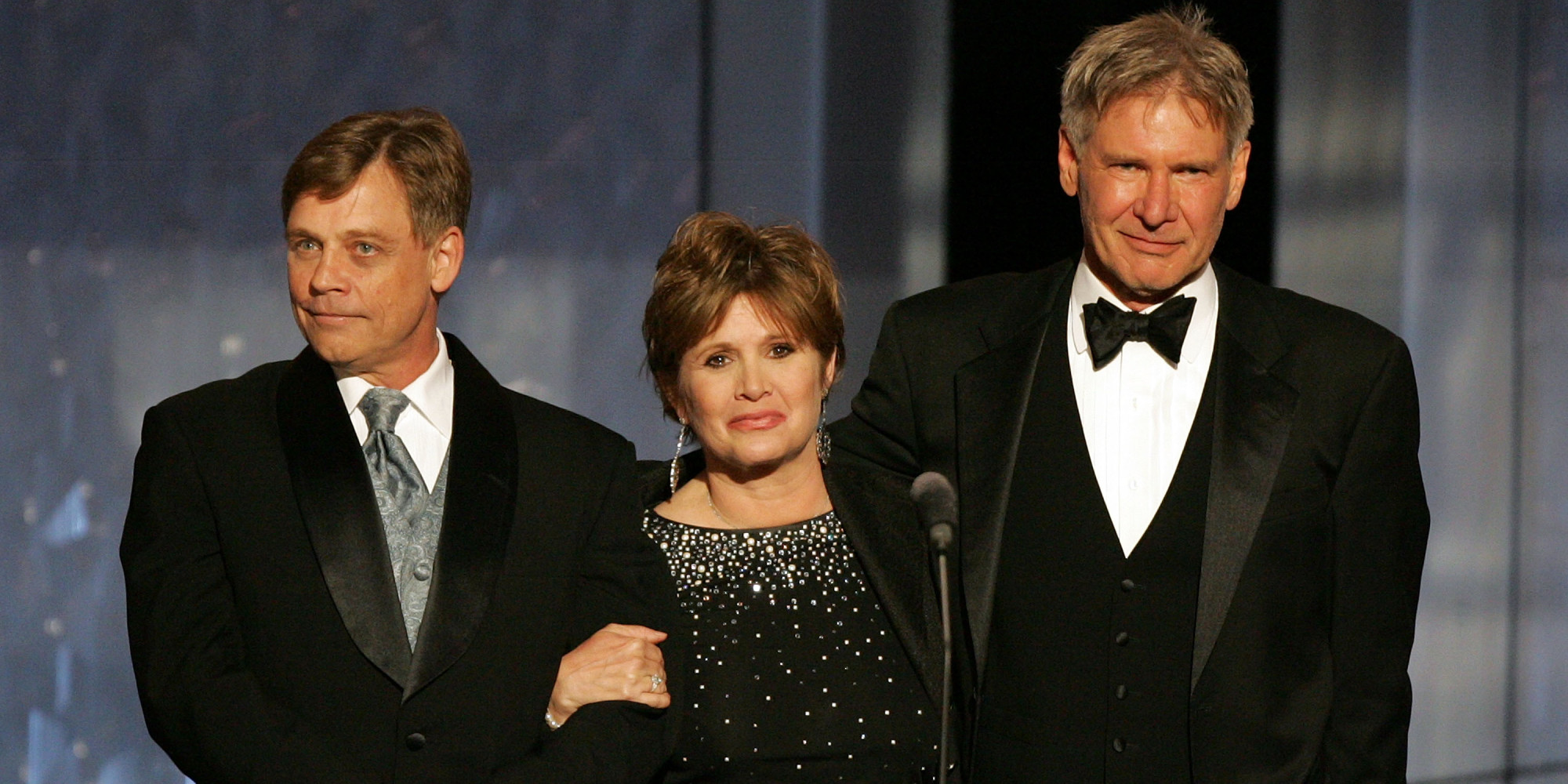 HOLLYWOOD - JUNE 09: (L-R) Actors Mark Hamill, Carrie Fisher and Harrison Ford speak onstage during the 33rd AFI Life Achievement Award tribute to George Lucas at the Kodak Theatre on June 9, 2005 in Hollywood, California. (Photo by Kevin Winter/Getty Images)
